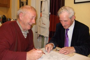 Two elderly men smiling and looking at a map on a table