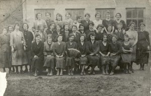 Black and white photo of large group of women in three rows in front of building